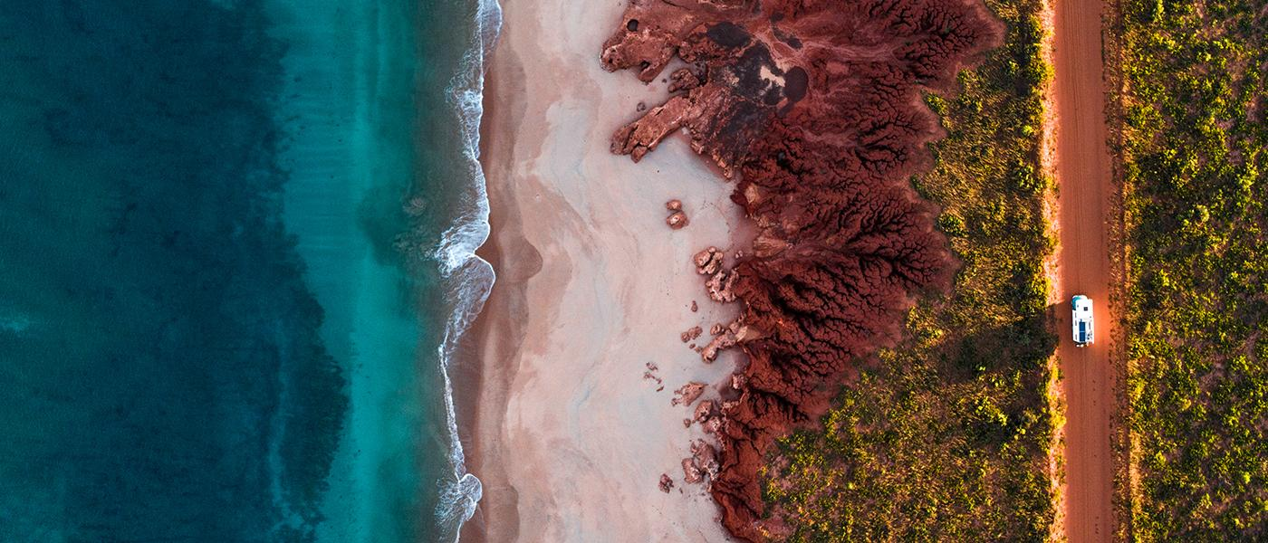 Aerial shot of coastline with red dirt track and car.