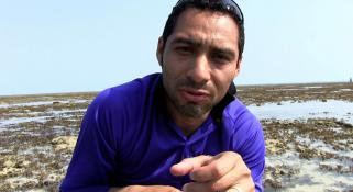 Oliver Gomez talking to camera, crouched down on a reef