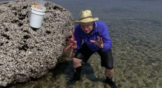 Merrick Ekins holding a sea star, crouching up to his ankles in water on a reef