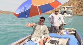 Rodrigo on a small dingy with using the Darlek to capture information from the sea under an umbrella