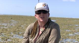 Zoe Richards wearing a hat and sunglasses talking about the corals on a reef
