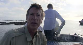 Clay Bryce talking to camera sitting in a small boat with man standing behind him steering