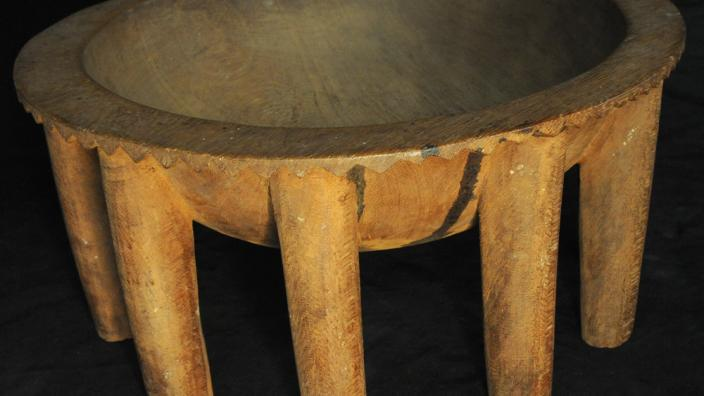 A large wooden kava bowl with many table-like legs
