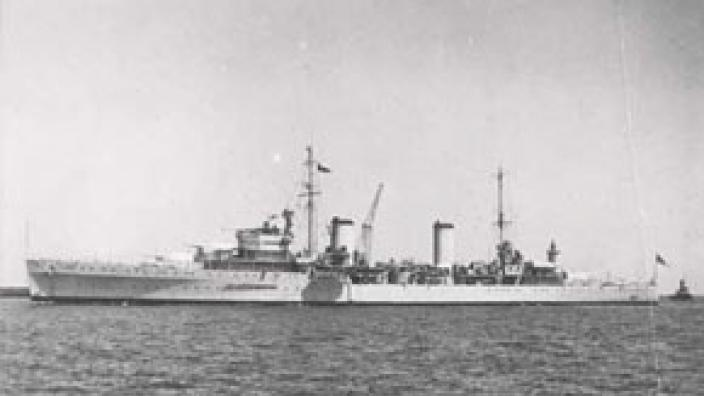 Port side view of white HMAS Sydney (II) viewed from a distance at sea
