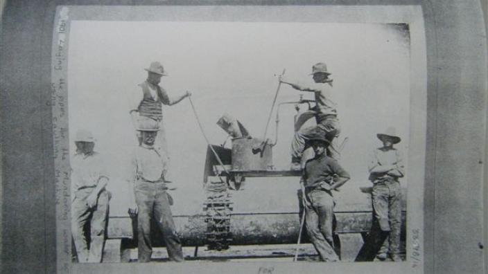 Men preparing lead jointing for pipe, c.1900s