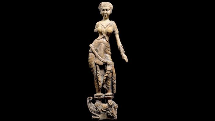 STATUETTE OF A WOMAN STANDING ON A MAKARA, BEGRAM. IVORY. 1ST–2ND CENTURIES AD