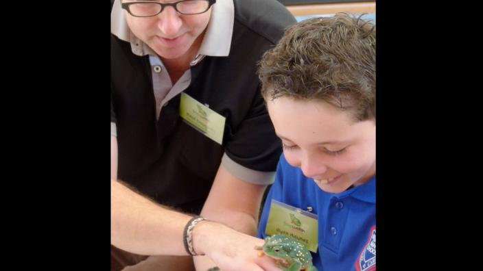 A child being presented with a live frog