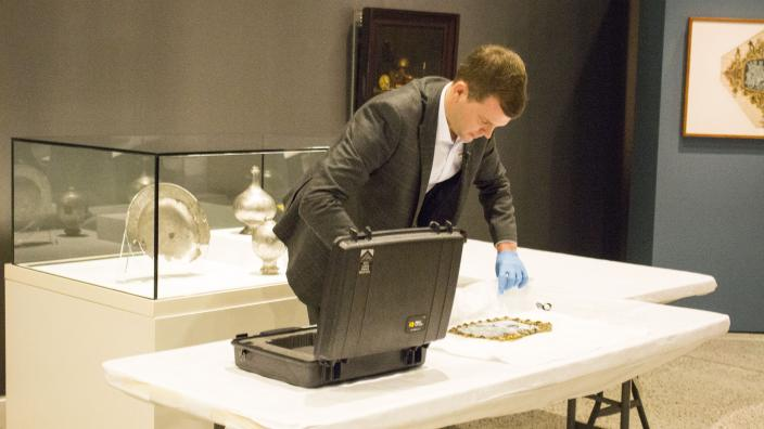 Curator Ben van den Burcken carefully unpacks the cameo for installation