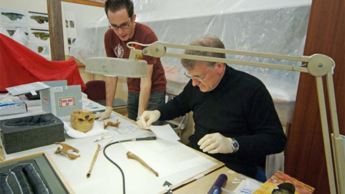 Two archaeologists at work preparing papers