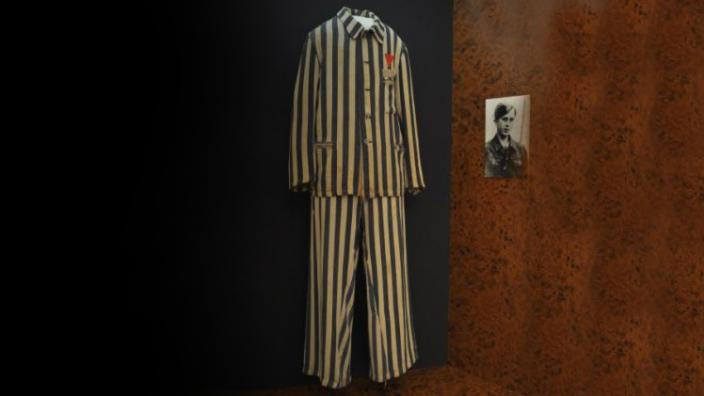 A museum display of a uniform worm in a concentration camp