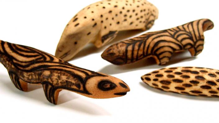 A series of wooden animals with hot wire impressed patterns
