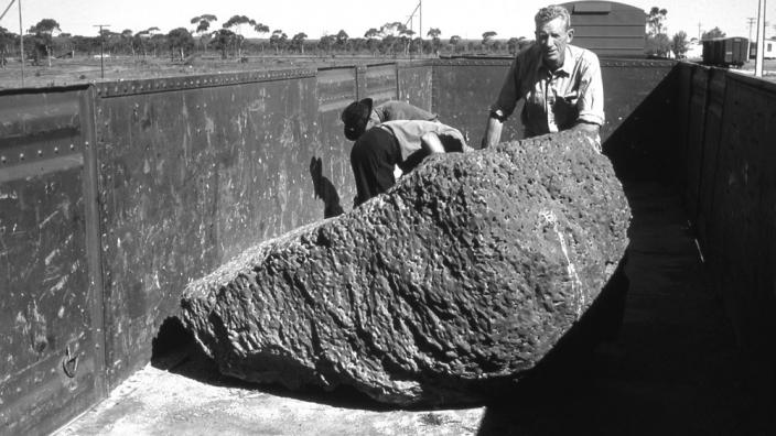 A scientists examining a meteorite in the field