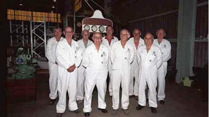 A group of mean wearing white, gathered in a huddle