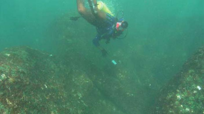 A diver working on a cannon at shipwreck site