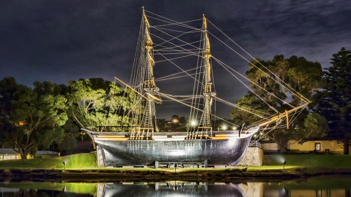 """""""The Brig Amity at night. Its reflection can be seen in the water."""""""