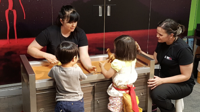 Museum staff interacting with two children at the Discovery Zone.