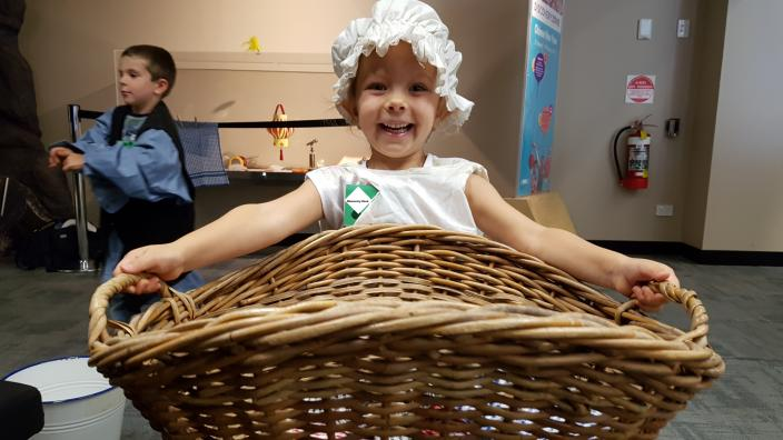"""""""A child is dressed in a """"olden day"""" outfit, and is holding a large basket."""""""