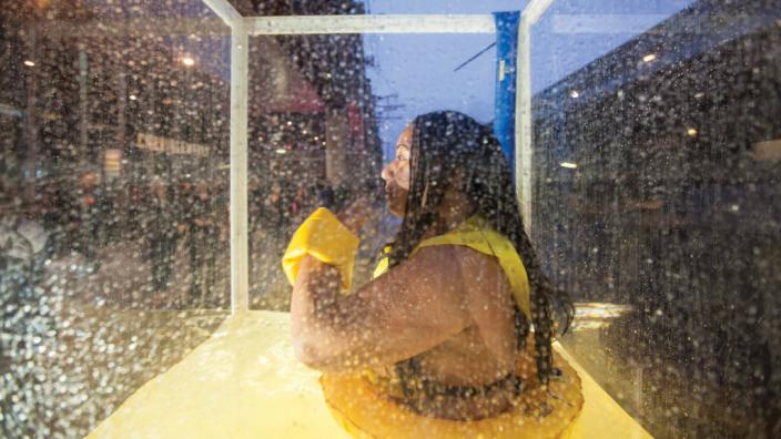 """""""A woman sitting in an enclosed tank of water."""""""