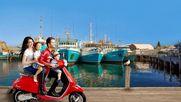 """A family ride a Vespa on a jetty"""