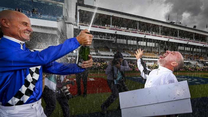 """""""Two jockeys are celebrating a victory by popping a bottle of champagne."""""""