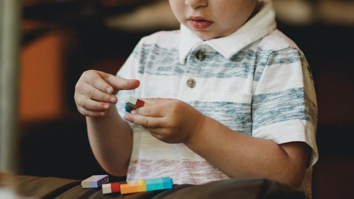 """""""A toddler playing with lego pieces."""""""