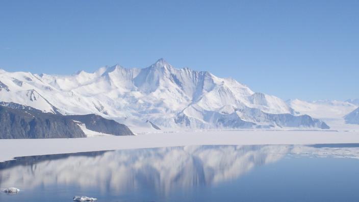 """""""A panoramic shot of a glacial lake with crisp blue skies in Antarctica."""""""