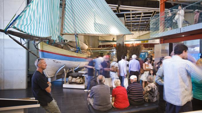 """""""The Hooked on Fishing gallery with crowds of people around an Indonesian fishing boat."""""""
