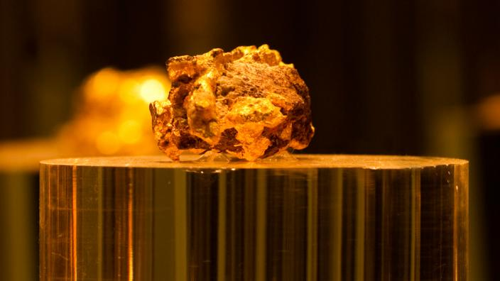 A large gold nugget on a podium