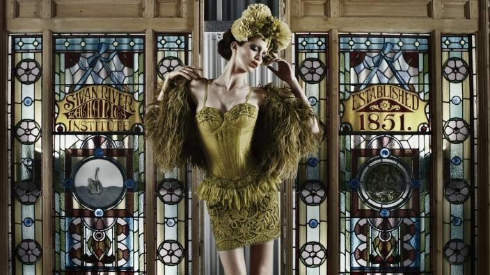 Model wearing Aurelio Costarella's garments standing in front of stained-glass windows
