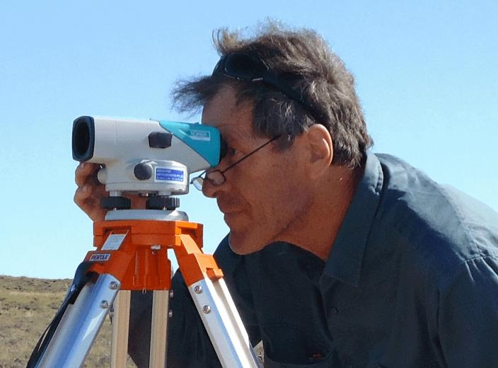 Dr Bill Humphreys measuring the landscape with a surveying tool