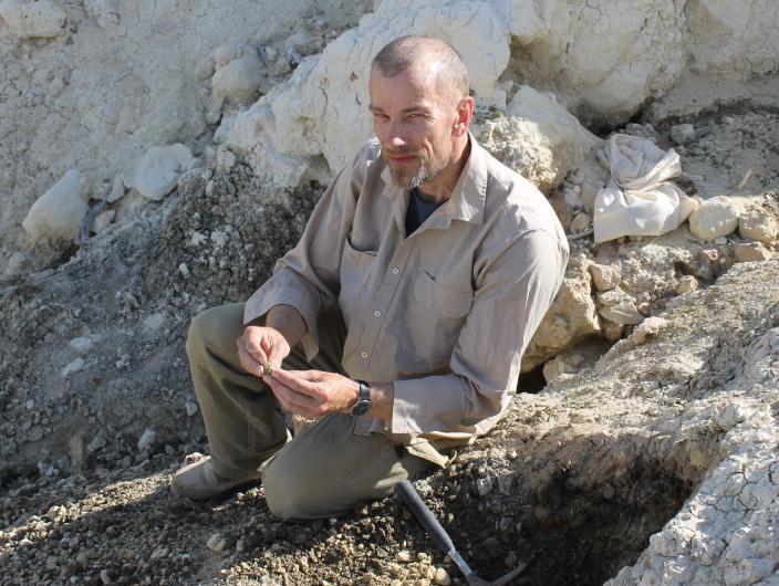 A person doing fieldwork holding an object