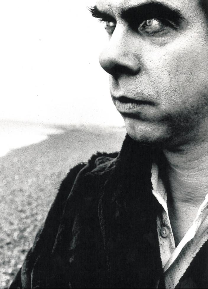 Close up Nick Cave with intense on Hove, UK beach with stones in the background