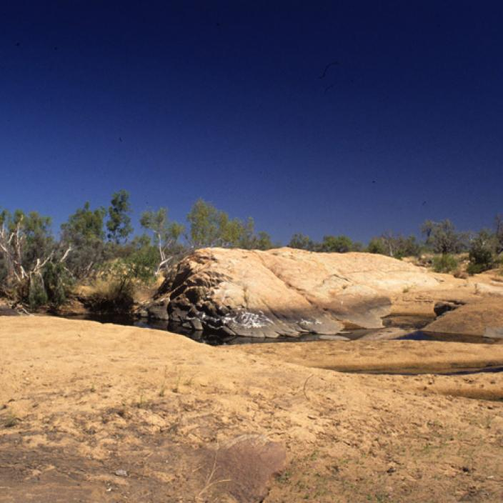 Rolling dry hard ground with small water oasis under a harsh hot sun