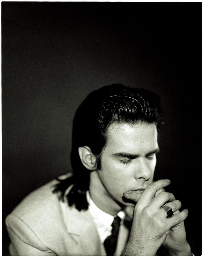 Nick Cave in a prayer pose.