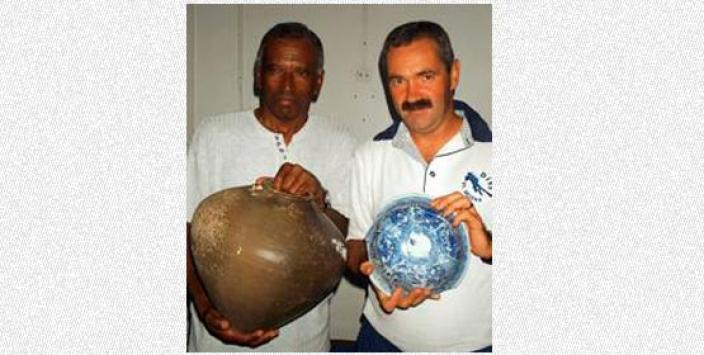 Two people holding items recovered from the wreck