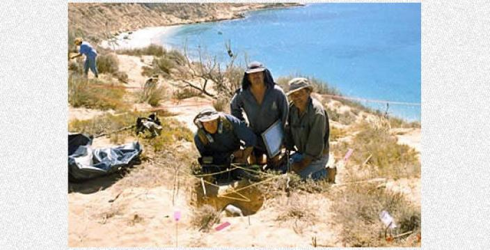 Three scientists posing near an excavation site