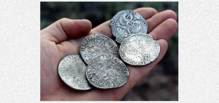 A hand holding five large silver coins