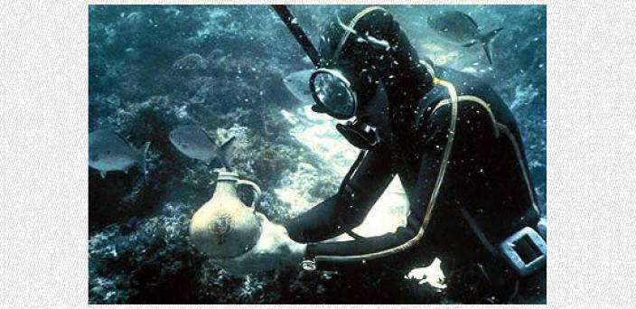 Diver holding an undamaged piece of stoneware