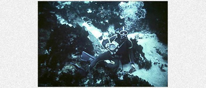 Diver holding an early underwater camera