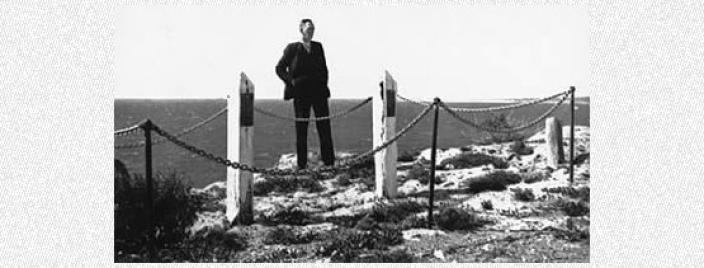 Man standing next to memorial posts