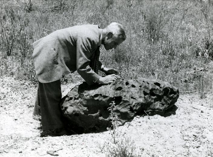 Image of a man inspecting a large meteorite