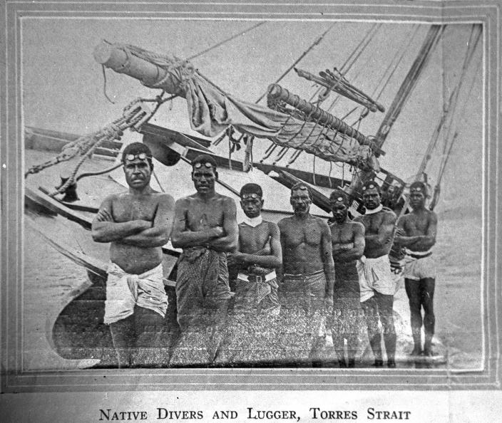 Image of a group of people standing in front of a boat