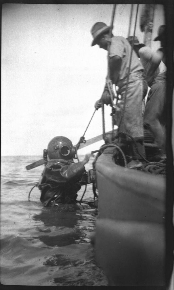 Image of a person hauling a diver out of the ocean