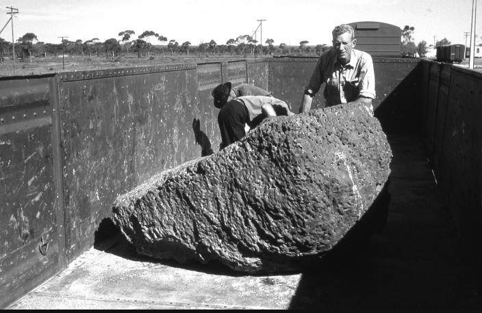 Image of two men standing next to a massive meteorite