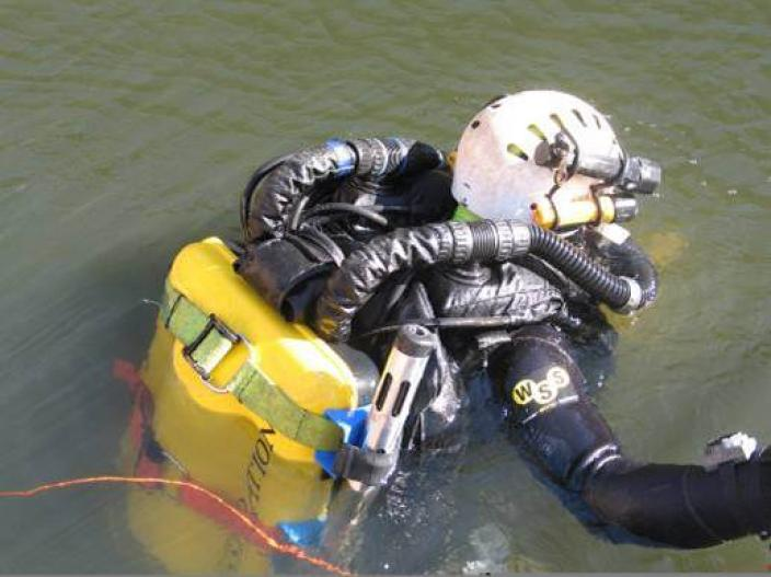 A diver sitting at the surface of the water