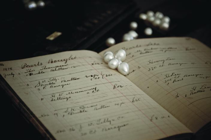 Image of pearls scattered on a business ledger.