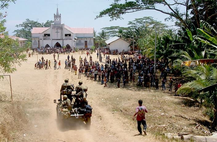 A 3 SAS Squadron vehicle mounted patrol are welcomed by East Timorese locals