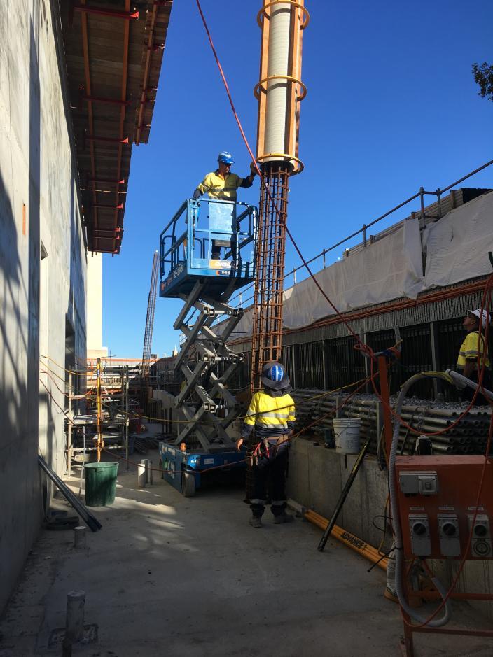 Worker on scissor lift guiding reinforced column to worker below