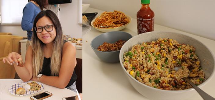 Woman sits eating fried rice, bowl of fried rice and hot sauce.