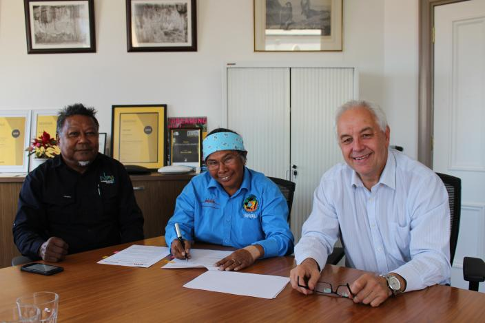 Three people at a boardroom table smile for the camera while one signs a documen
